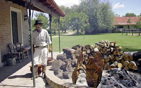 Gaucho qui veille sur l'asado à l'estancia Ombu de Areco
